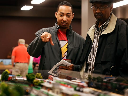 Michael Snead (left) watches a model railroad layout