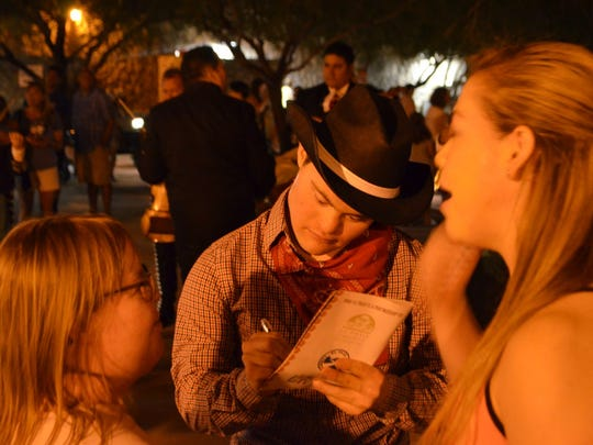 """Hernandez signs an autograph for a fan after a performance of """"Viva! El Paso."""""""