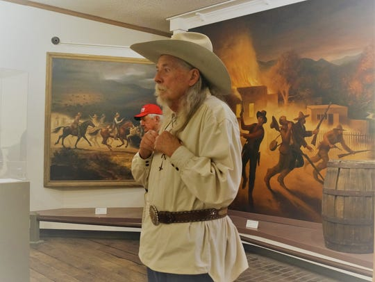 Shuster with painting 'Chasing Billy the Kid' by Peter