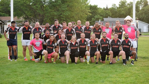 Local rugby players pose for a group photo after a