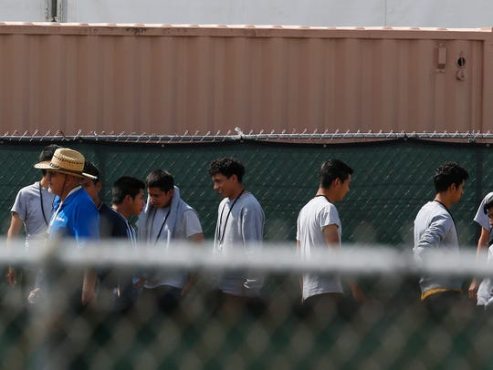 Migrant children walk outside at the Homestead Temporary