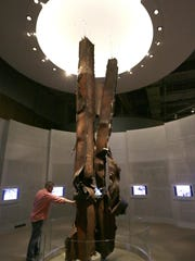 """FILE - In this Friday, Sept. 11, 2015 file photo, Landon Cole reaches out to touch steel beams from the World Trade Center on display at the The George W. Bush Presidential Library and Museum in Dallas. """"They are the relics of the destruction and they have the same power in the same way as medieval relics that have the power of the saints,"""" said Harriet Senie, a professor of art history at the City University of New York and author of """"Memorials to Shattered Myths: Vietnam to 9/11."""" (AP Photo/LM Otero)"""