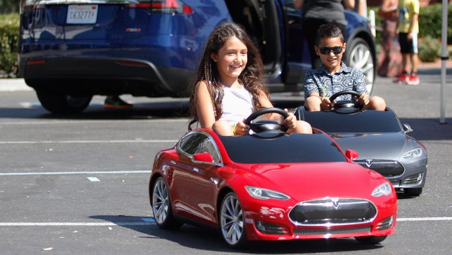 Baran Eshaghi and Bobby Baghari ride in mini-cars at the Tesla exhibit Saturday during the Blue Sun Festival at the Westlake Golf Course.