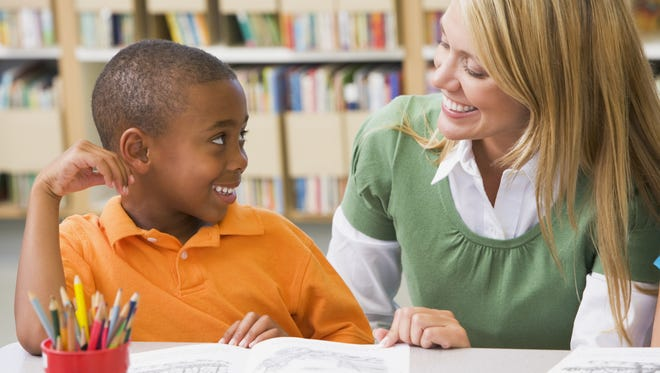 A kindergarten teacher helps a student with his reading skills