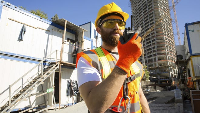 A construction worker using a two-way radio device
