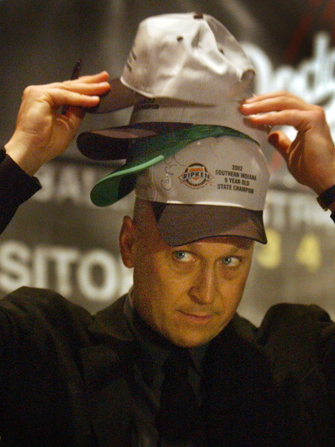 Cal Ripken Jr., places hats on his head as he prepares to autograph them for kids after a large press conference announcing a Class A baseball team in Evansville in 2003.