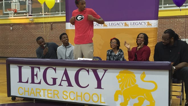 Legacy Charter School senior Nicolas Claxton reveals a University of Georgia T-shirt after announcing Monday that he will sign to play basketball for the Bulldogs as family members look on in the Legacy gymnasium.