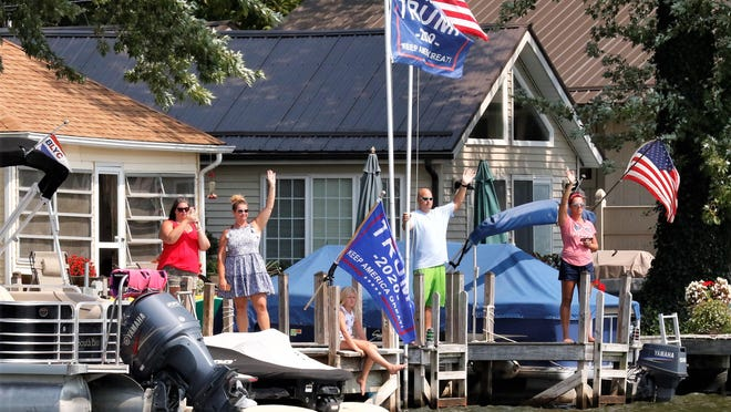 Jessica Bean, second from the left, stands with friends and family as they wave to the boat parade passing her Buckeye Lake home on Monday, Sept. 7. Hundreds of boats participated, travelling along the shore from Liebs Island past the Cranberry Bog State Nature Preserve.