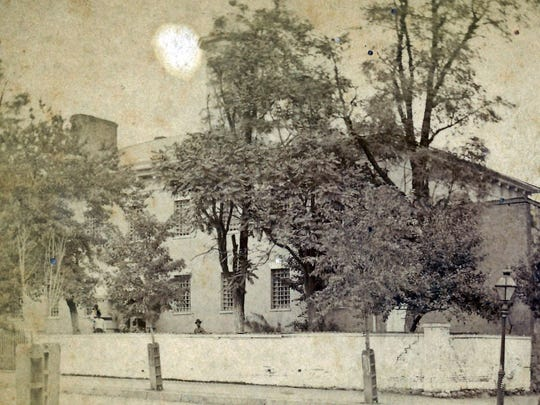 The Old Jail at North Second and East King streets around 1880. Note all the trees and the exterior wall around the front. The cupola is behind the tree.