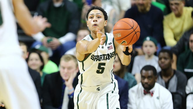 Bryn Forbes of the Michigan State Spartans looks to pass against the Oakland Golden Grizzlies at the Breslin Center on December 14, 2014 in East Lansing.
