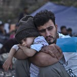 A Syrian refugee child sleeps in his father's arms while waiting at a resting point to board a bus in this photo from Oct. 4, after arriving on a dinghy from the Turkish coast to the northeastern Greek island of Lesbos.