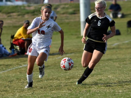 Centennial's Tia Gladem (white) runs down a loose ball as the Hawks took on Hobbs on Tuesday night at the Field of Dreams Soccer Complex. For a roundup of Tuesday's high school sports action, click on this story at lcsun-news.com.