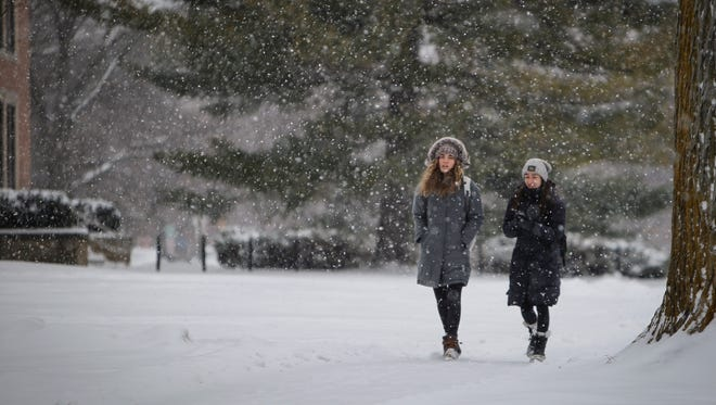 MSU students Abby Brodeur, left, and Nicole Sarkisian make their way across a snow laden campus Wednesday, Dec 13, 2017.