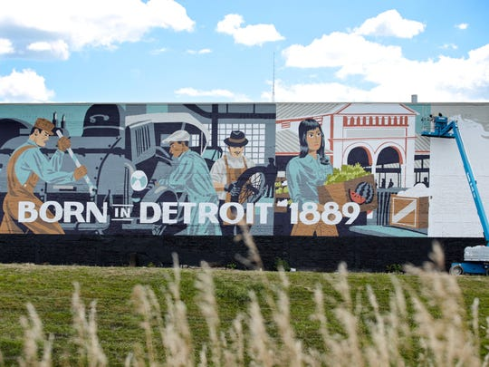 Kelly Golden, 28, and Jordan Zielke, 28, both of New Baltimore, Mich, work on a new mural on on Monday, Aug. 24, 2015, on the wall of the new Carhartt store in Detroit.
