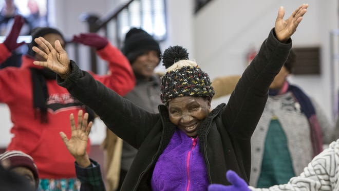 Kwirina Ngeze throws her arms up in joy as she and other refugees participate in a yoga exercise to start the morning at Highland United Methodist Church. The exercise, at the beginning of classes, is part of the Countywide Refugee Elder Program. Jazz. 30, 2018.