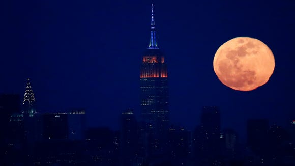 The full moon rises behind the New York City skyline