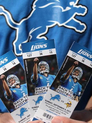 Detroit Lions fans hold their tickets before they enter Ford Field prior to the start of their home opener against the Minnesota Vikings, Sunday, Sept. 8, 2013.