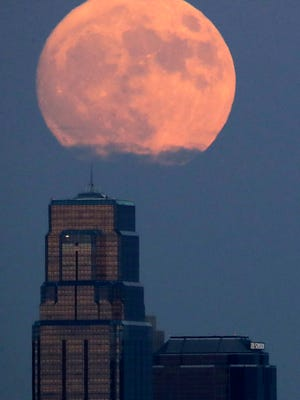 The moon rises beyond downtown buildings Sunday, Nov. 13, 2016, in Kansas City, Mo. Monday's so-called supermoon will be extra super - it will be the closest the moon comes to us in almost 69 years. And it won't happen again for another 18 years.