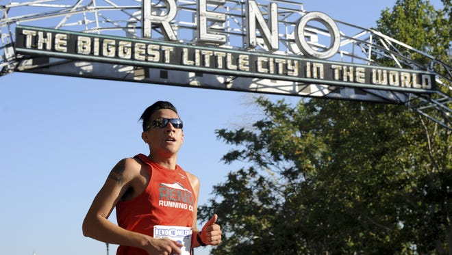 Luis Barraza passes beneath the old Reno Arch on Lake Street during the inaugural Reno 10 Miler race last year.