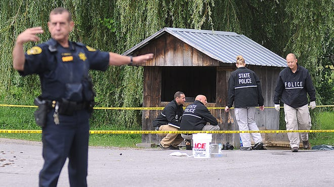 New York State Police crime scene investigators search for clues at a roadside vegetable stand in Oswegatchie, N.Y., on Thursday, as they investigate the abduction of two Amish sisters. Delila, 7, and Fannie Miller, 12, were reported as being abducted from the stand around 7:30 p.m. Wednesday.