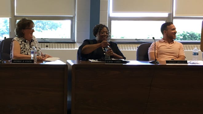 Elected Muncie school board members Jason Donati, Kat Carey (center) and Debbie Feick give farewell comments at a meeting on Friday.