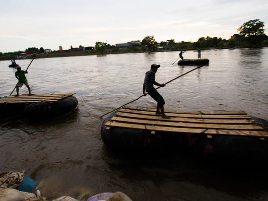 River runners work their floats on the Suchiate River between Tecun Uman, Guatemala and Mexico on June 21.  Migrants typically cross illegally using these floats, while black-market goods flow south.