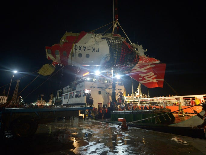 Indonesian personnel hoist a section of recovered wreckage