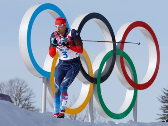 FILE - In this Feb. 23, 2014 file photo Russia's gold medal winner Alexander Legkov skis past the Olympic rings during the men's 50K cross-country race at the 2014 Winter Olympics in Krasnaya Polyana, Russia. The Court of Arbitration for Sport ruled on Thursday, Feb. 1, 2018 to reinstate Leskov as gold medal winner of the men's 50-kilometer cross-country skiing which he was stripped of on doping allegations earlier. (AP Photo/Dmitry Lovetsky)