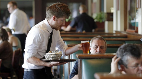 A waiter serves drinks in this June 3, 2014 file photo. An Alabama hosue committee Wednesday heard arguments for a bill that would ban cities in the state from setting their own minimum wages.