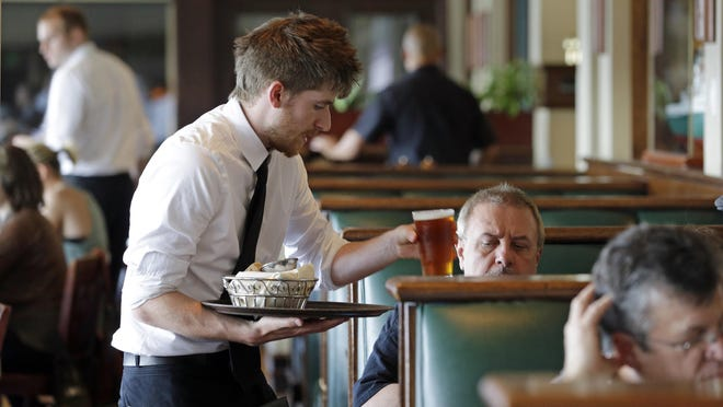 A waiter serves drinks in this June 3, 2014 file photo.