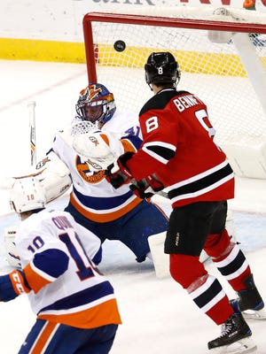 New Jersey Devils right wing Beau Bennett (8) watches as his shot enters the net of New York Islanders goalie Jaroslav Halak, of Slovakia, during the third period of an NHL hockey game, Saturday, April 8, 2017, in Newark, N.J. The Islanders won 4-2. (AP Photo/Julio Cortez)