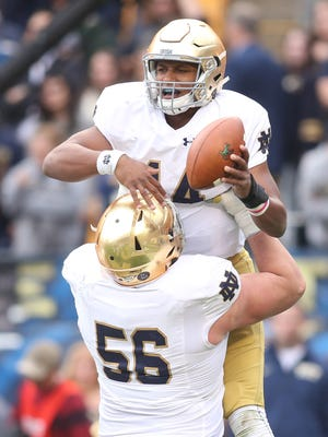 Notre Dame Fighting Irish quarterback DeShone Kizer (14) and offensive lineman Quenton Nelson (56) celebrate a touchdown by Kizer against the Pittsburgh Panthers during the fourth quarter at Heinz Field.