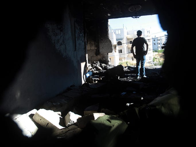 A Palestinian inspects the damaged home of Amer Abu Aisheh, a suspect in the kidnapping and murder of three Israeli teenagers, on July 1 after the Israeli army burned the building in Halhoul, West Bank. Israel believes alleged Hamas members named Marwan Qawasmeh and Amer Abu Aisheh abducted and shot the three teenagers.