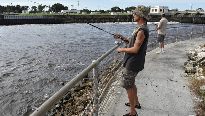 "Zach Trahan (front), of Port St. Lucie and his twin brother Eben Trahan, of North Carolina, try their luck fishing  July 9, 2018 downstream of the St. Lucie Lock and Dam. ""We catch and release; we throw them back,"" Zach Trahan said."