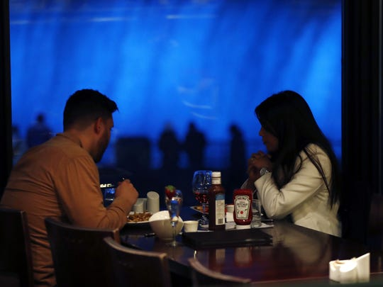 In this Saturday, Dec. 10, 2016, a couple dines at the Elements Cafe overlooking the Niagara Falls illuminated by new LED lights, in Niagara, Ontario. Visitors unwilling to brave the frigid air outdoors can watch Niagara Falls illuminated after dark from the windows of hotels and restaurants on the Canadian shore. (AP Photo/Julio Cortez)