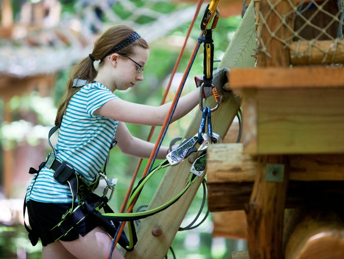 Elizabeth Rutalis, 12, climbs a ladder to the main platform of the aerial adventure park at the summit of Bristol Mountain on Wednesday, July 2, 2014.