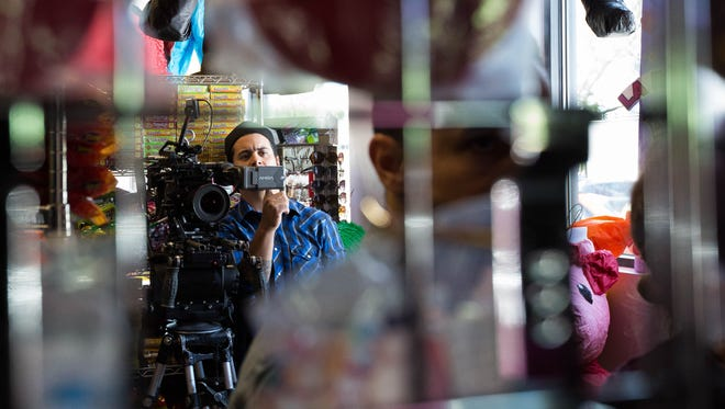 Filmmaker Michael Garcia looks over a scene while filming a movie inside a Las Cruces ice cream shop in May.
