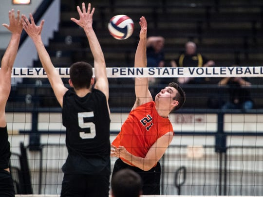Northeastern's Cole Brillhart (21) leaps up to spike
