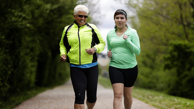 Lorena Justiniano (right) who was diagnosed a few years ago with a hereditary condition that is eroding her vision, runs with guide Allison Leer on the Monon Trail in Carmel.