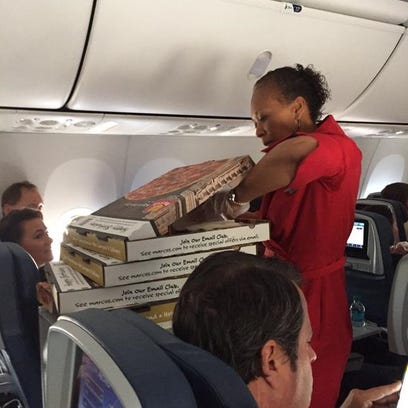 A Delta flight attendant passes out passengers to delayed passengers on a flight that diverted to Knoxville, Tenn., on May 26, 2015.