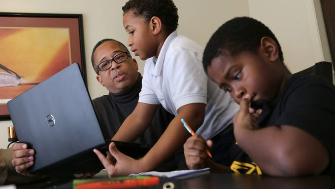 Logan, 10, in the fifth grade works on math homework. In the background is his dad, Ernest Robinson, 51, as he helps his son Connor, 12, in the seventh grade, search the internet for information on Greece for a report as part of his homework at their home in Southfield.