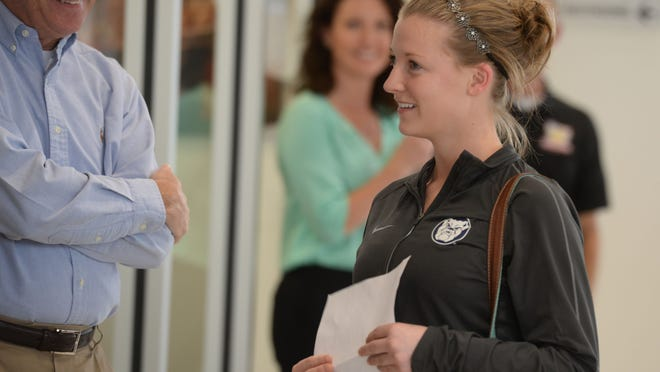 """Garry Kleer, left, watches as Kelsey Cupp learns she can choose between a car or a scholarship during the """"School is Cool"""" giveaway at Wetzel Cheverolet Thursday, May 14, 2015, in Richmond."""