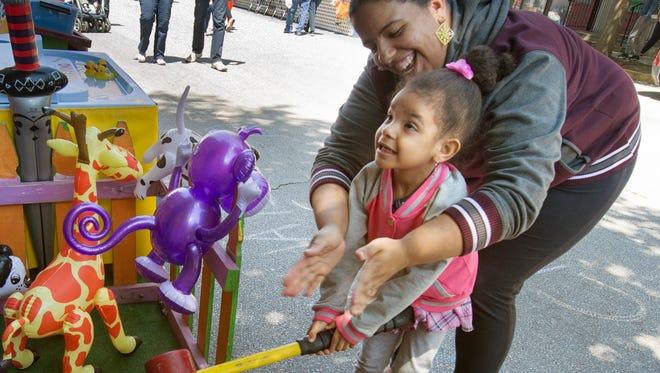 Jorgina Feliciano, top, of York, helps her daughter Yasmin Washington, age 3, win a prize during the 41st Annual Olde York Street Fair.
