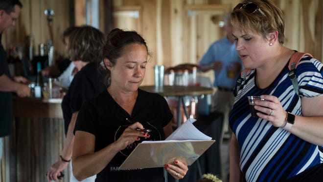 Owner Katy Groves-Mussat passes out the petition to resident Latasha Biggs at Farmer & Frenchman Winery on Thursday, June 7, 2018.