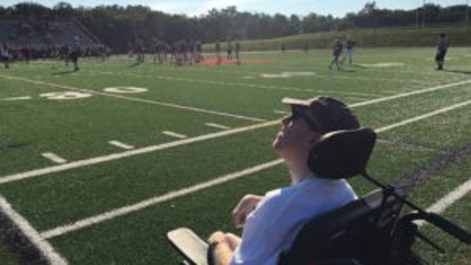 Geoffrey D'Aries, a Mendham alumnus with cerebral palsy, watches the football team from the sidelines. (Courtesy of Jeanne D'Aries)