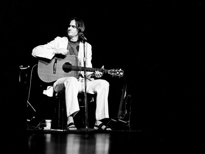 James Taylor, dressed simply in a white suit, dark T-shirt and sandals, sits down after walking out without introduction onto the stage of the new Grand Ole Opry House on May 14, 1974.