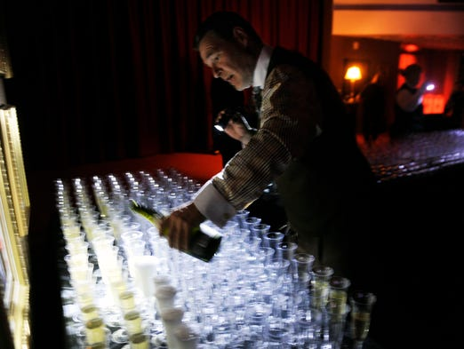 Ira Luther help fills 1,000 champagne glasses for TPAC's season announcement party.