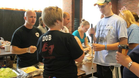Members of the Brockport Police Department serve lunch to athletes at Camp Abilities in 2012. photo by Caurie Putnam