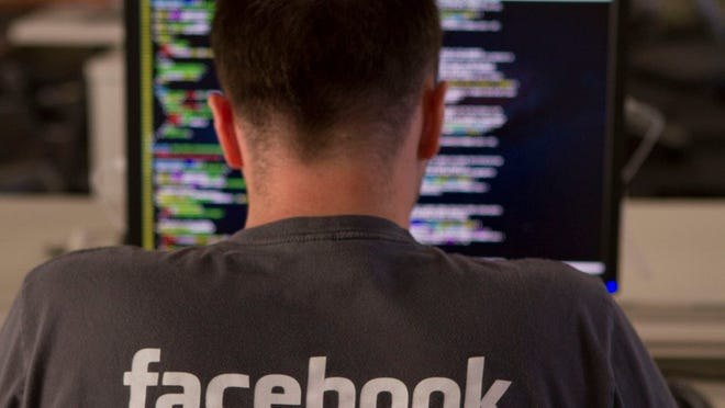 A Facebook engineer inputting code on his laptop.
