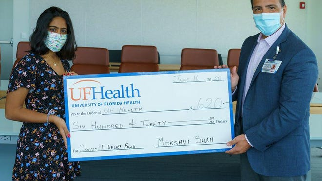 Mokshvi Shah presents UF Health Shands CEO Ed Jimenez with a $620 donation for the UF Health COVID-19 relief fund.